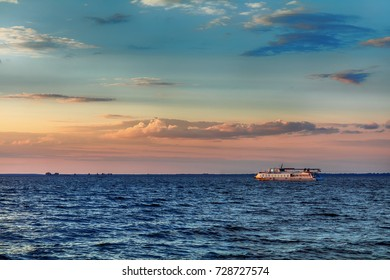 Amazing colors of the sky before sunset over the river in the summer time. Tourist boat is on the beautiful blue water. Dnieper river