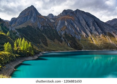 amazing colors of water on the lake Morasco with the shadow of the plants reflected and mountains in background in autumn season