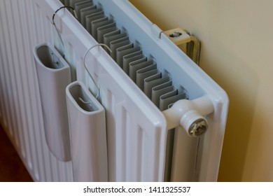 Amazing composition of indoor wall heater, warmer or radiator. With two white water reservoir, tank or holders on it. Attatched to yellow wall with control screw visable.