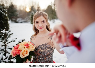 Amazing couple in winter fairytale forest in love. Girl in red beautiful dress. Valentine's Day theme.