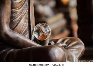 Amazing crystal ball in hands of monk statue, detail and close up of crystal sphere, buddhism symbol, feng shui, shining star, out of focus subject