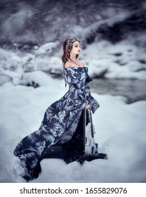 Amazing cute slim young woman in chic fairy tale image in gray puffy dress and with crown on her head holds beautiful white violin and bow against background of white snow covered forest