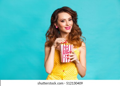 Amazing cute young pretty girl on the turquoise background eats popcorn, dressed in a bright yellow body dresses, perfect makeup and hairstyle, fashionable Pin up girl, cool, smiling, hollywood