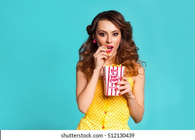 Amazing cute young pretty girl on the turquoise background eats popcorn and surprised looking at the camera, wearing a bright yellow body dresses, fashionable Pin up girl, cool, smiling, hollywood