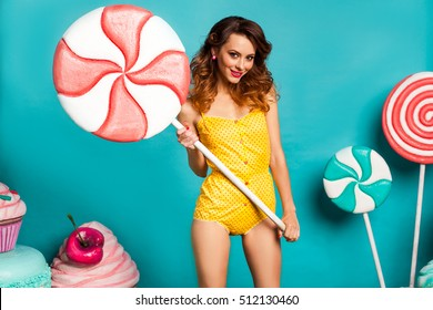 Amazing cute young pretty girl on the turquoise background holding a Huge sweets, Cake, candy, bright yellow body dresses, perfect makeup, hairstyle, fashionable Pin up girl, cool, smiling, hollywood