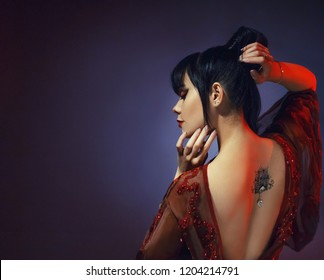 amazing dark-haired sexy tender graceful princess of Japan, a young girl in a light red dress with an open back and a lotus tattoo with a precious stone. art processing photo with blue background.