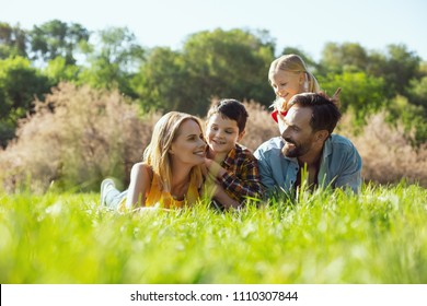 Amazing day. Happy pretty mother lying in the grass with her family and smiling