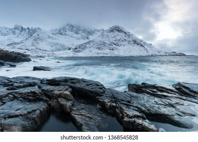 Amazing day in Mountains And Fjords, Winter Landscape, Norway Clouds sky on the Norwegian Alps and the blue hour begins in range at Senja, Norway. Beautiful christmas time near Troms county.