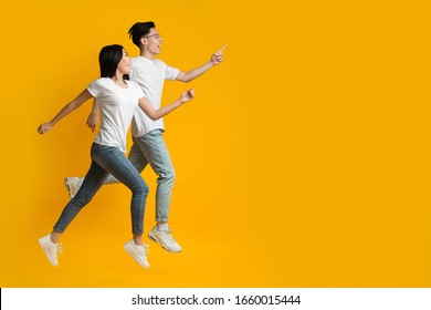 Amazing deal. Excited asian couple running towards copy space, yellow studio background