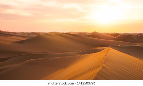Amazing desert sunset. Beautiful Arabian desert with warm colors. Colorful contours of sand dunes at Abu Dhabi.