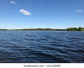 Amazing desolate lake waves white cloud at blue sky, wild forest and forested hill wilderness skyline, tranquil pure nature of Kuusamo Finland tourism travel vacation