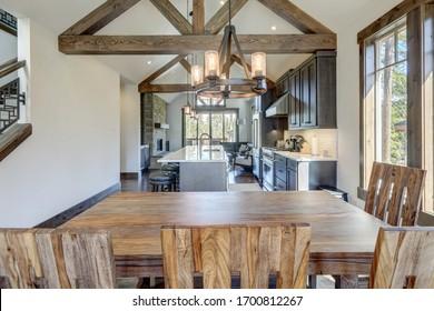 Superbe salle à manger près de la cuisine luxueuse moderne et rustique avec plafond voûté et poutres en bois, longue île avec contrefort blanc et armoires en bois foncé.