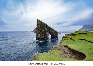 Amazing dramatic view of Drangarnir gate in front of Tindholmur in Vagar island, Faroe Islands, Denmark north atlantic ocean, best destination for hiking, stunning sea stack with deep blue water.