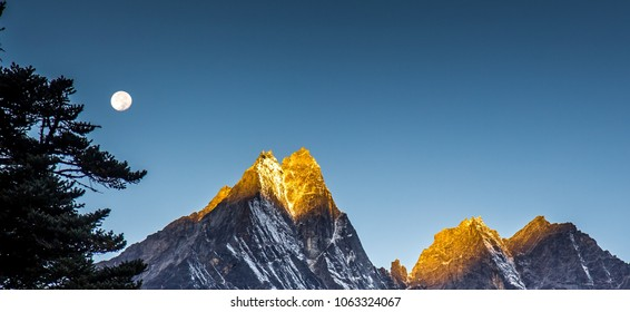 Amazing early morning: golden sun lights high peak of Kongde Ri mountain of the Himalaya, one of the most difficult mountains to climb. Moon shines above the summit. Himalayas, Nepal