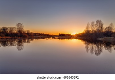 Amazing early spring landscape of a marsh with a water pond. Sunset on the bog lake. Nature of Estonia.