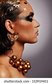 Amazing egyptian golden make-up, Cleopatra style, profile portrait,smokey eyes,golden glamour, shiny, jewelry and art.