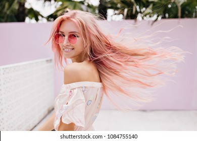 Amazing european girl with pink hair dancing on the street. Attractive white lady in sunglasses fooling around in summer.