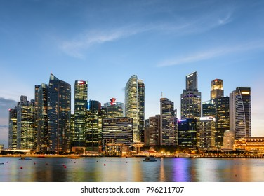 Amazing evening view of downtown in Singapore. Wonderful skyscrapers and other modern buildings are visible on blue sky background. Colorful city lights reflected in water of Marina Bay.