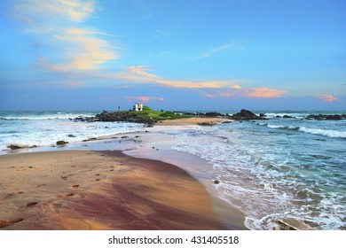 Amazing evening view - small island with Buddhist shrine and colorful sandy beach against the background of beautiful sunset sky and Indian ocean in Tangalle (Tangalla) beach, Sri Lanka, South Asia