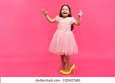 Amazing excited happy girl in dress in mama`s shoes expressing to camera isolated on pink background. Brightful emotions