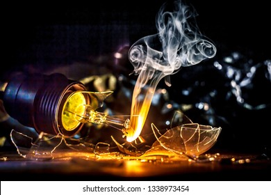 Amazing explosion of burning light bulb with splinters of broken glass and smoke on isolate black background. Сoncept of creative art illustrations of tungsten filament combustion in contact with air