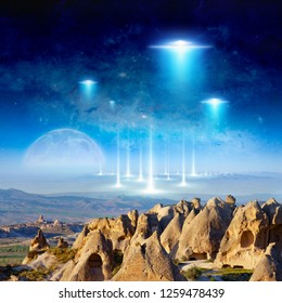 Amazing fantastic background - extraterrestrial aliens spaceship fly above surreal terrain, full moon rises above the horizon. Elements of this image furnished by NASA