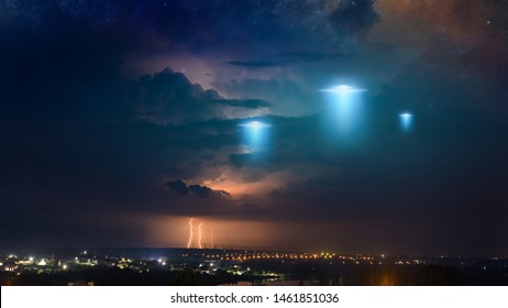 Amazing fantastic background - extraterrestrial aliens spaceship fly above small town, ufo with blue spotlights in dark stormy sky. Elements of this image furnished by NASA