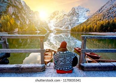 Amazing fascinating magical autumn winter landscape with a girl playing guitar over a lake on Fanes-Sennes-Braies natural park in the Dolomites, Alps, Italy. (meditation, relaxation – concepn)