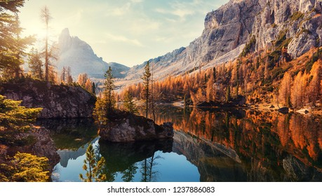 Amazing Federa lake, natural Scenery, during Sunrise. Awesome Landscape. Foggy Dolomites Alps with forest under sunlight. Travel in nature. Beautiful sunrise with Lake and majestic Mountains.