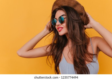 Amazing female model with romantic hairstyle touching her hat and looking away with pensive face expression. Studio shot of glamorous girl in sunglasses and tank-top.