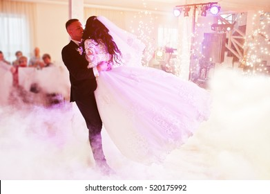 Amazing first wedding dance of newlywed with different colorful light, cold fire with fireworks and heavy smoke on restaurant.