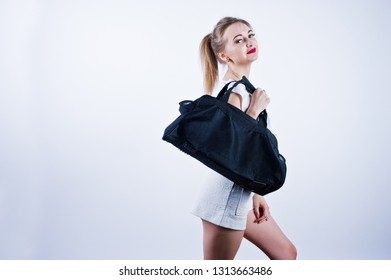 Amazing fit sexy body brunette caucasian girl posing at studio against white background on shorts and top with black sport bag.