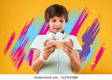 Amazing game. Progressive curious boy standing with a modern smartphone and feeling interested while playing exciting video games