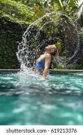 Amazing girl in a blue bikini in the swimming pool outdoors on the green trees background. She makes the spiral from the water splashes with her hair. Vertical.