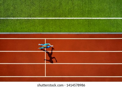 Amazing girl in a blue sportswear and sneakers runs on the running track at the stadium outdoors. Sun shines onto her body. Top view aerial photo. Horizontal.