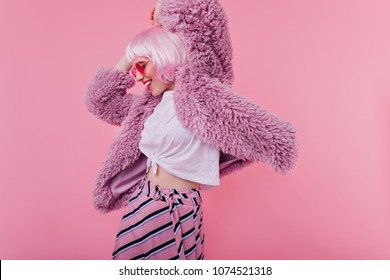 Amazing girl in purple jacket having fun during indoor photoshoot. Studio portrait of cute female model in sunglasses and pink peruke dancing and laughing.