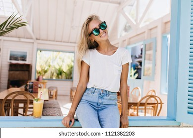 Amazing girl with tanned skin posing with orange cocktail. Smiling blonde woman in sunglasses sitting on window sill in summer morning.