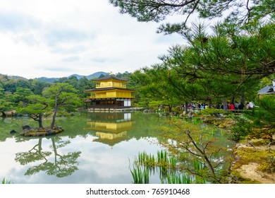 Amazing golden temple pavillion with reflection on water in the garden when spring with cloudy sky, Kinkakuji is zen buddhist temple and very famous travel destination in Kyoto, japan