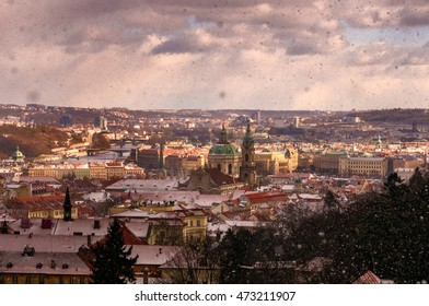 Amazing Gothic church of Our Lady and St. Nicolas church during winter day with heavy snow storm and sun rays peeping through clouds, Prague, Czech republic