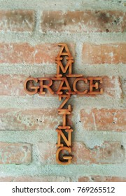 Amazing grace letters in a cross shape hanging on brick wall.