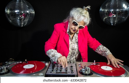 an amazing grandma DJ, older lady djing and partying in a disco setting