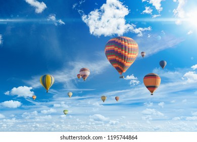 Amazing heavenly background - colorful hot air balloons fly in blue sky with white clouds and bright sunshine
