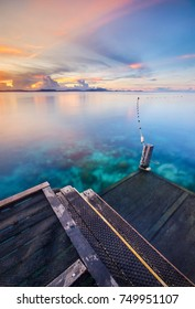 Amazing hue of colorful Mabul Island Sabah in sunset moment with crystal clear sea water and wooden jetty. Motion of the clouds and wave are observed due to long exposure shot. Nature composition
