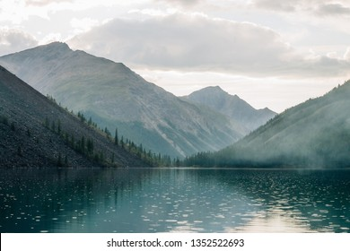 Amazing huge cloud above giant mountains. Raindrops on mountain lake. Beautiful rain drops. Wonderful droplets on lake water. Low clouds. Cloudy sky. Wonderful atmospheric ghostly highland landscape.