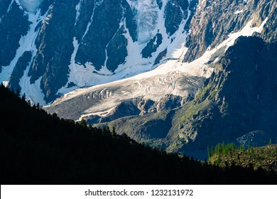 Amazing huge glacier above forest close up. Snow on mountainside. Giant wonderful snowy mountains in sunlight. Atmospheric minimalist mountain landscape of majestic nature in sunny day.