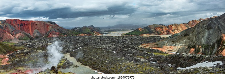 Amazing Icelandic landscape of colorful rainbow volcanic Landmannalaugar mountains, at famous Laugavegur hiking trail with dramatic snowy sky, hot steam valves and lava field in Iceland.