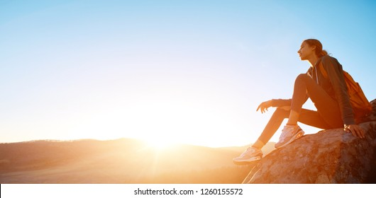 amazing image of a pretty woman hiker with small orange backpack sits on edge of cliff against background of sunrise