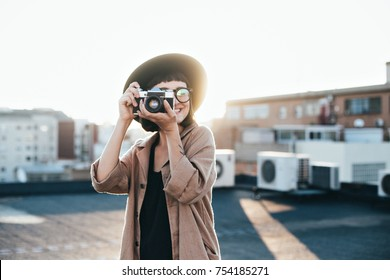Amazing and inspirational shot of young creative soul or artist posing or making photo with vintage analog retro camera on rooftop full of warm summer sunlight flares, cute and beautiful woman