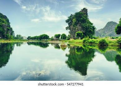 Amazing karst towers and green trees reflected in water of the Ngo Dong River at the Tam Coc portion, Ninh Binh Province, Vietnam. The Tam Coc is a popular tourist attraction in Asia. Toned image.