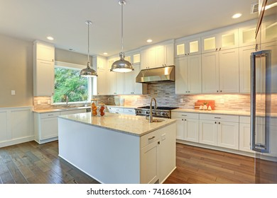 Amazing kitchen design with white shaker cabinets paired with marble counters, large kitchen peninsula and high-end stainless steel appliances.